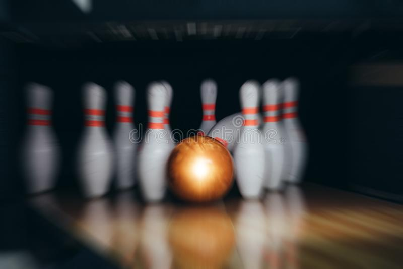 Motion blur of bowling ball and skittles on the playing field.  royalty free stock image