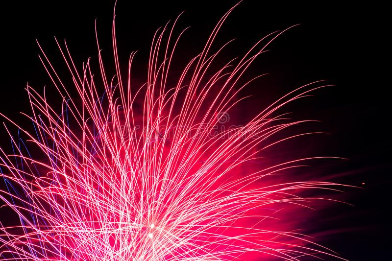 Single Pink Fireworks Show 4th of July. Motion blur of dynamic fireworks show. Lines of neon light, ashes, sparks, and more. independence day. Clouds filled with royalty free stock photography