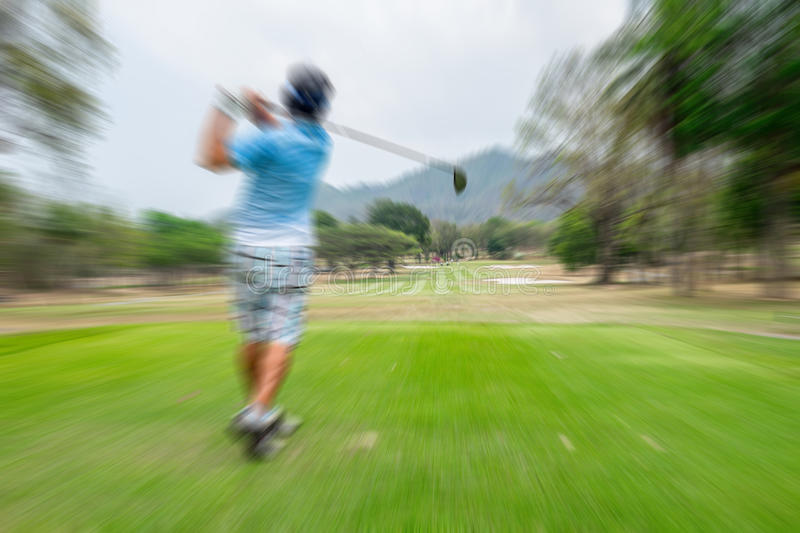 Motion blur golfer swinging driver. Club on teeing ground sending golf ball to fairway stock images