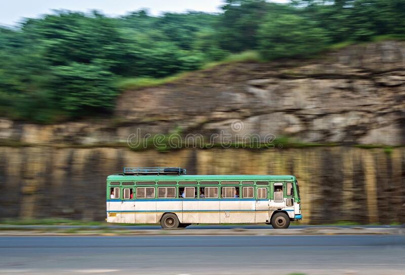 Motion blur image of non air-conditioned intercity bus in Maharashtra, speeding on highway street. Isolated , slow shutter speed panning image of a speeding bus royalty free stock images