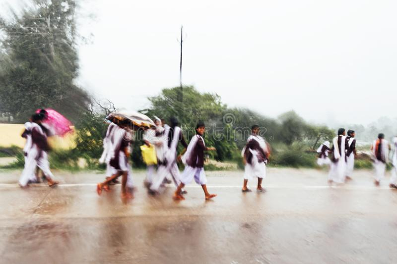 Motion blur of Indian students walking in the rain on the road. They are going to school bus while raining stock photo
