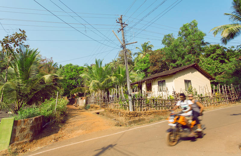 Motion blur from motorbike with tourists driving on village in popular Goa state, India. Rural landscape. Motion blur from motorbike with tourists driving on stock image