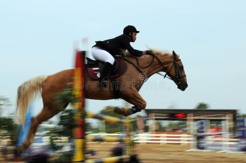 Motion blur unidentified equestrian rider show jump horse trying to overcome hurdles at Malaysia sport, Sukma in Pahang royalty free stock photo