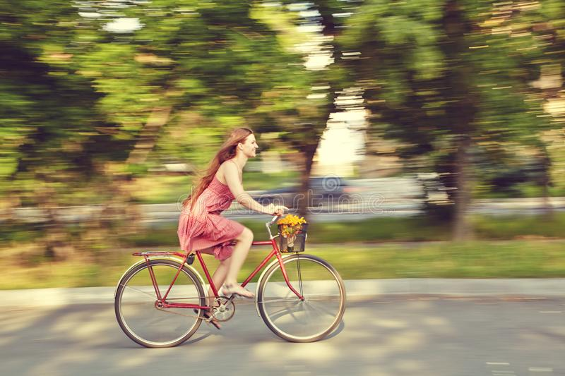 Motion blur. young woman in a dress rides a bike in a summer park stock images