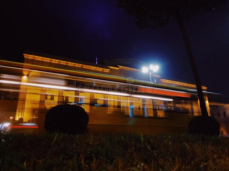 Motion blurred bus against Facade of Tbilisi parliament on Rustaveli avenue, Georgia. Motion blurred bus on Tbilisi main street, Rustaveli avenue, night view royalty free stock image