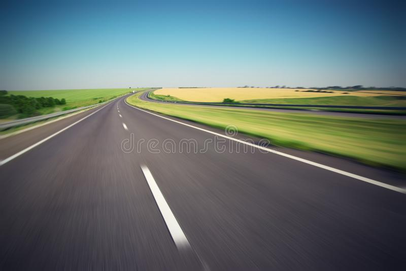Motion blurred empty highway with green meadow on horizon royalty free stock image