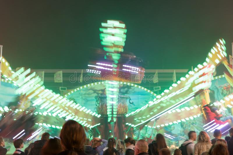 Motion blurred green illuminated fun ride stock image