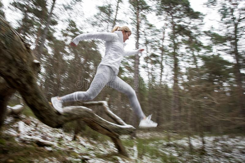 Motion blurred photo of woman exercising in forest in winter royalty free stock photo
