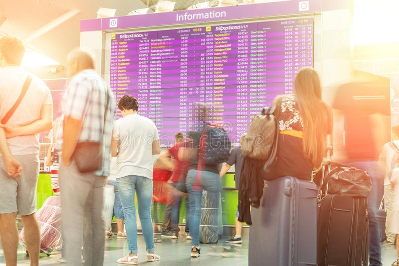 Motion blurred travellers crowd looking at fligh feparture and arrival timetable at airport terminal. Travel and tourism concept. Flight delay, departure royalty free stock image