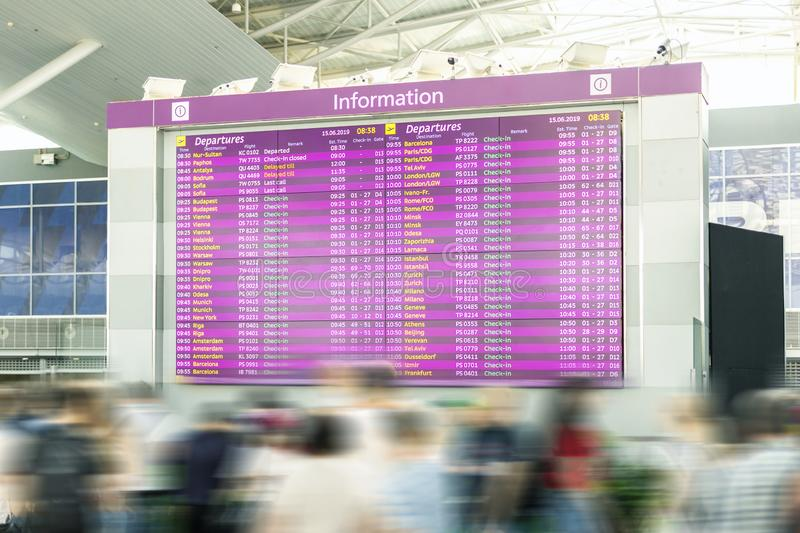 Motion blurred travellers crowd looking at fligh feparture and arrival timetable at airport terminal. Travel and tourism concept. Flight delay, departure stock photography