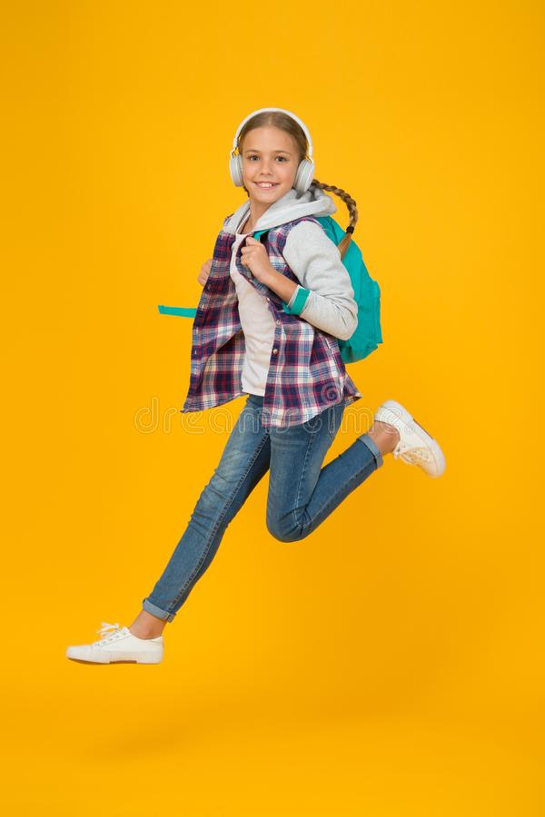 Always in motion. Energetic cheerful teen listening music. Stylish schoolgirl going to school. Girl little fashionable. Girl carry backpack. School daily life stock images