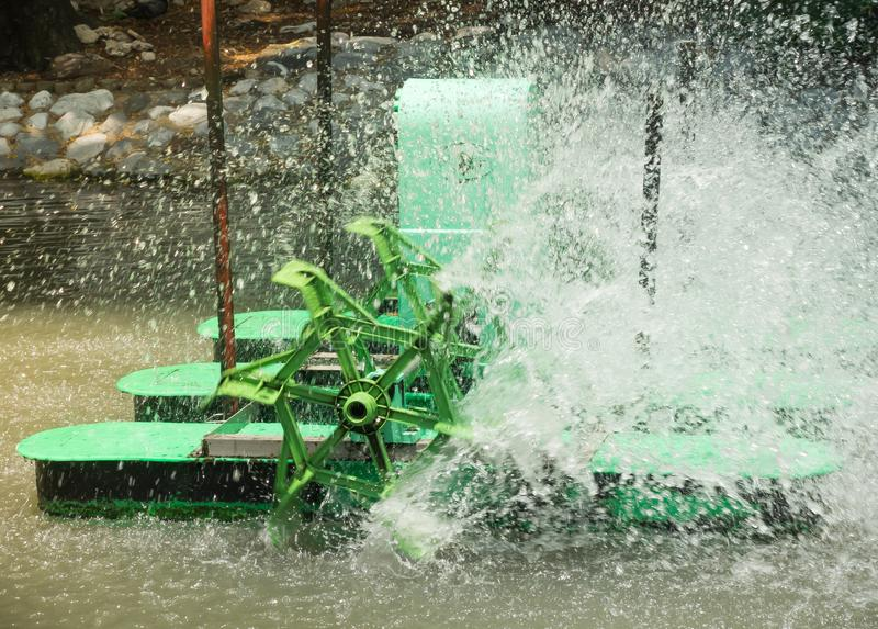 Motion image of water splashing by green farm water aeration system for Outdoor fish or shrimp farming pond. A Motion image of water splashing by green farm stock image