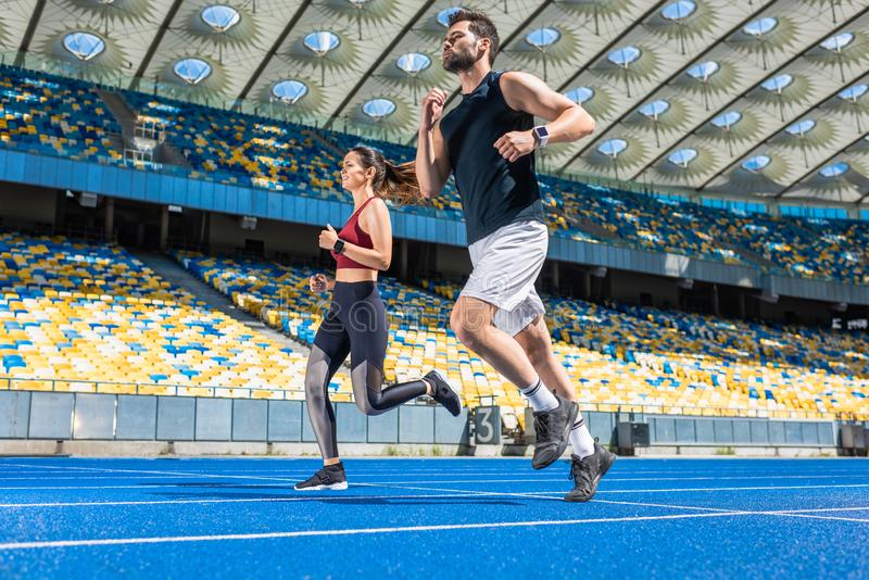 motion shot of young male and female joggers running on track stock image