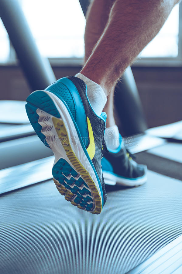 Motion and strength. Close-up part of man in sports shoes running on treadmill at gym stock images