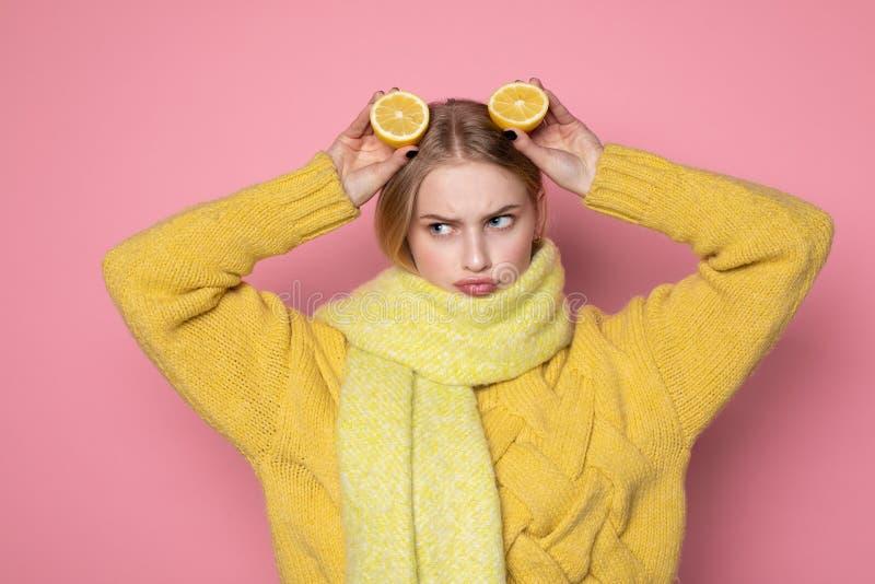 ?motions humaines Belle fille europ?enne blonde dans le visage dr?le jaune d'apparence de chandail et d'?charpe, tenant l'agrume  photos libres de droits