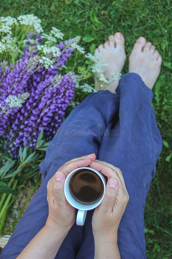 Motiv av en barfota kvinna som sitter i en trädgård med lösa blommor och en kopp kaffe fotografering för bildbyråer