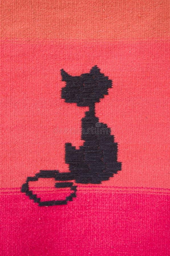 Motiv eines neuen roten gesponnenen Teppichs mit schwarzer Katze stockbilder