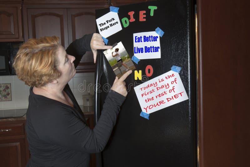 Motivación de dieta de la fijación de la mujer en el refrigerador foto de archivo