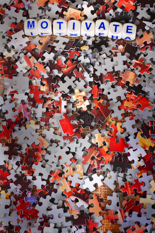 Motivate. Dice spelling out the word motivate laying on top of red and gray scattered puzzle pieces. Copy space royalty free stock image