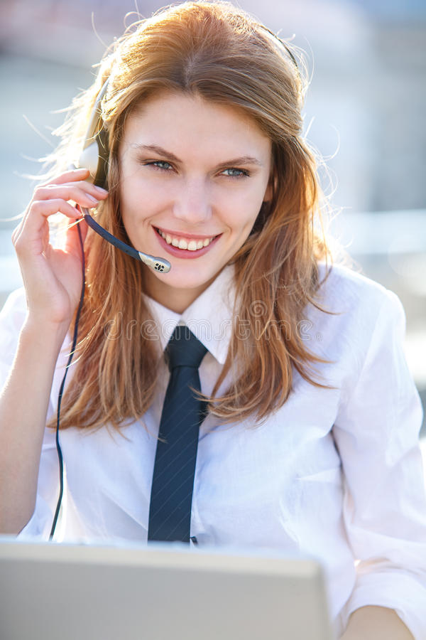 Motivate Call Center agent. Smiling brunette girl wears shirt and tie stock images
