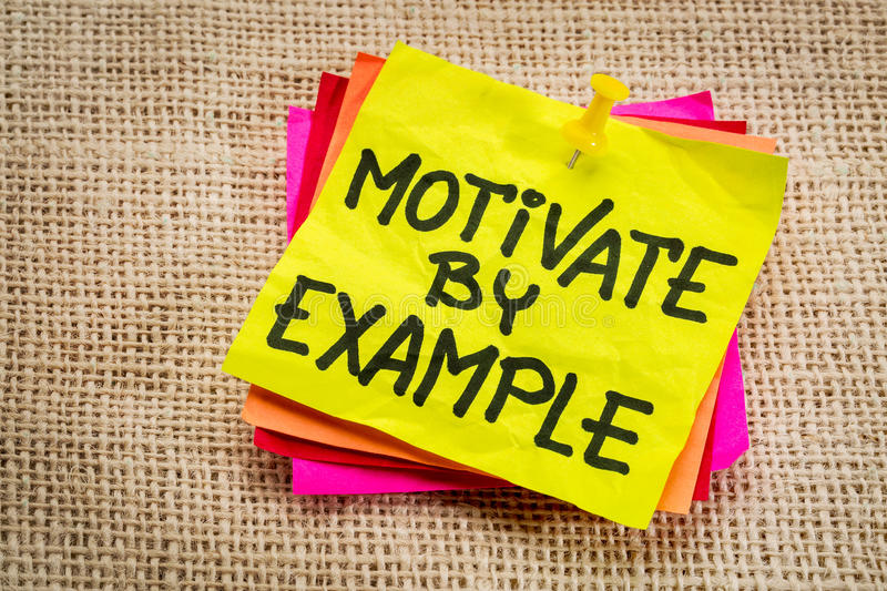 Motivate by example note. Motivate by example - advice or reminder on a yellow sticky note royalty free stock photography