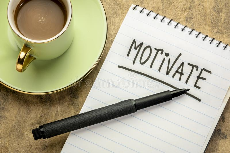 Motivate handwriting in spiral notebook. Motivate  -  handwriting in a spiral notebook with a cup of coffee stock images