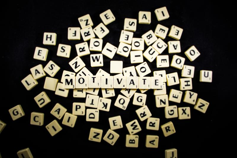 Motivate word spelled with letter tiles in black background stock image