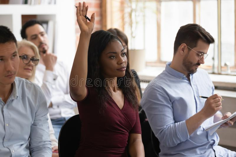 Motivated black female raise hand take part in training. Focused african American female employee raise hand volunteer answer question at team training in office stock photo