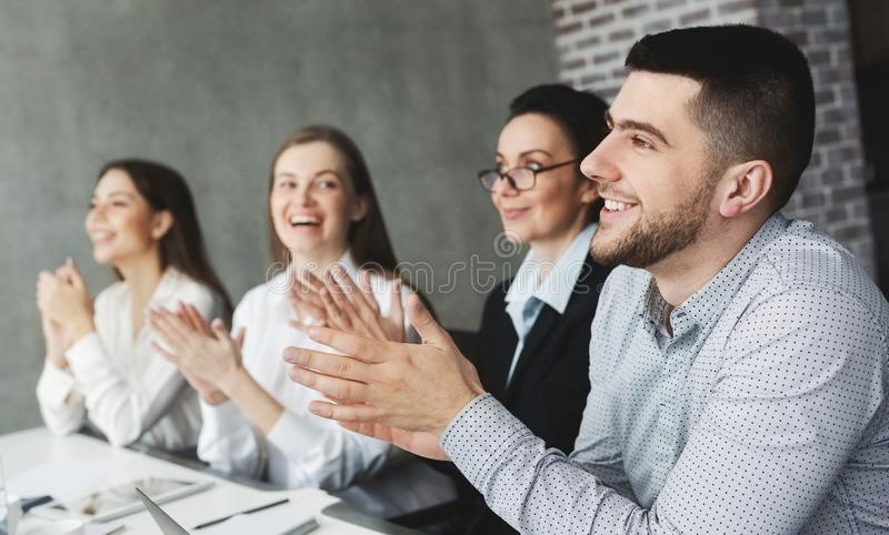 Motivated business team applauding after lecture to speaker stock image