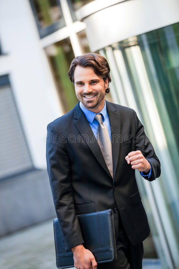 Motivated businessman punching the air stock photo