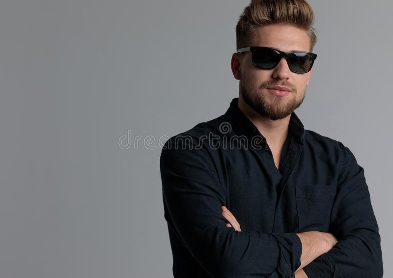 Motivated casual man holding his arms folded at his chest. While wearing a blue shirt and sunglasses, standing on gray studio background royalty free stock images
