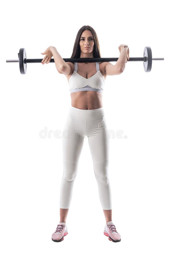 Motivated confident fitness woman holding barbell on her shoulder looking at camera. stock image