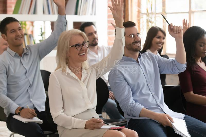 Motivated diverse employees raise hand participating in training. Motivated excited diverse employee raise hand taking part in teambuilding activity at company stock photography