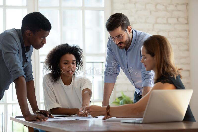 Diverse business team working together, discussing project documents royalty free stock photos