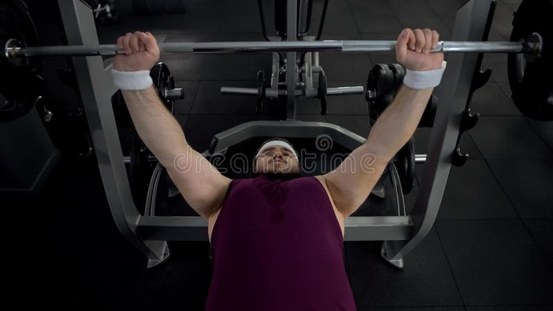 Motivated fat man lifting barbell, pumping-up his muscles, healthy lifestyle stock photography