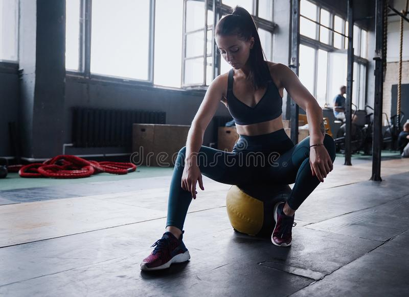Motivated female workout fitness club, sit gym smile camera, wipe sweat off forehead, lean medicine ball crossfit. Recreation, wellbeing and sport concept stock photo