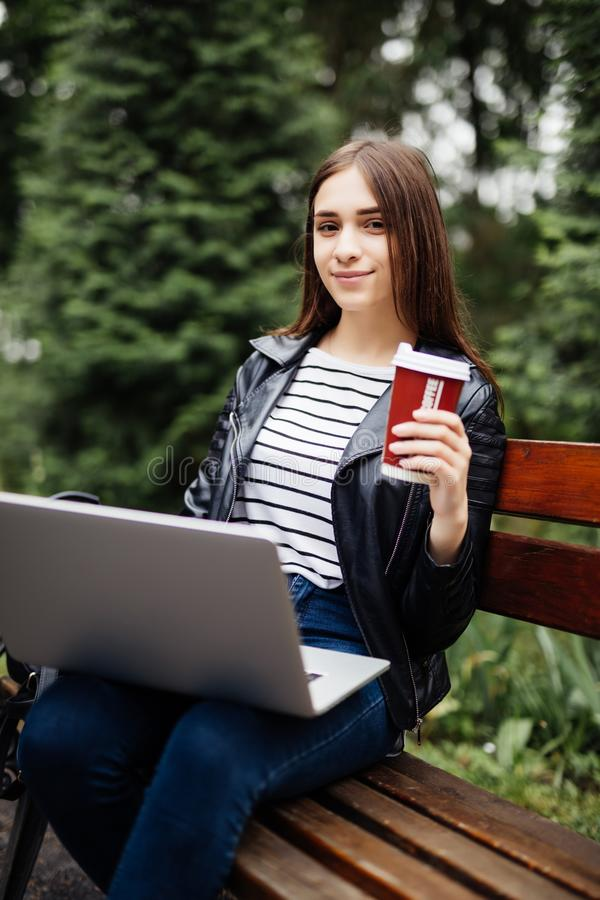 Motivated freelancer in the park. Young brunette girl on a bench, drinking coffee and working with laptop online. Lifestyle, techn stock image