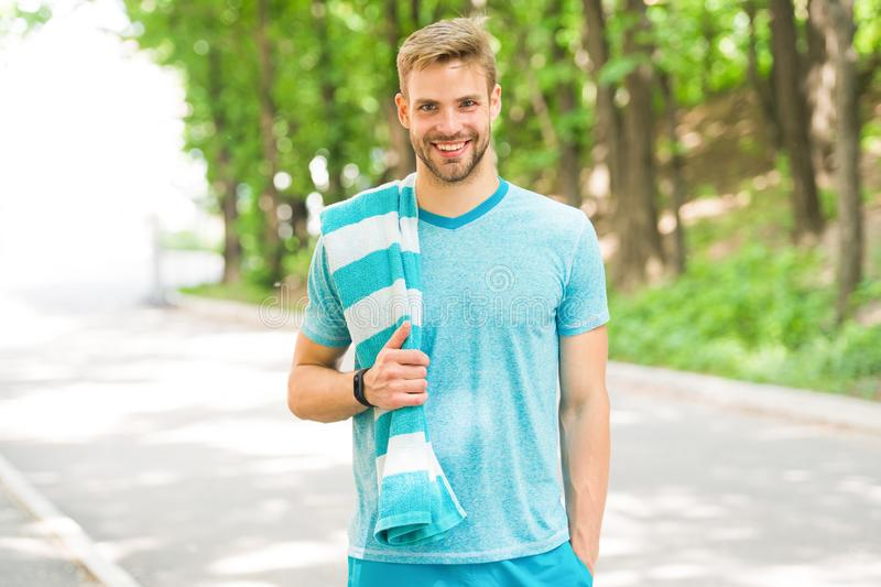 Motivated for morning training. Man athlete with towel nature background. Athletic man relaxing break. Athlete takes royalty free stock photography