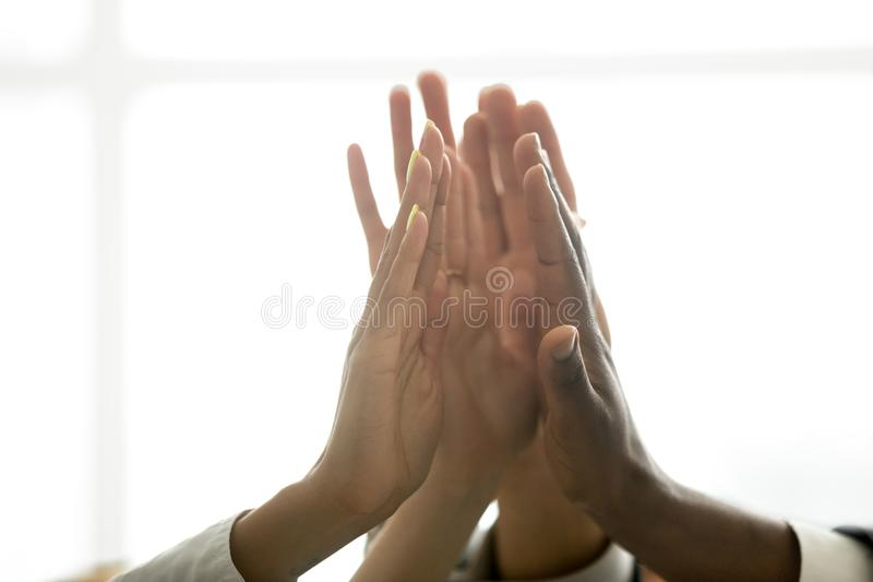 Motivated multiracial business team joining hands together givin. Motivated multiracial business team join hands palms together, black and white diverse people royalty free stock photography