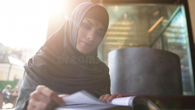 Motivated Muslim female student reading book in cafe modern education literature royalty free stock photography