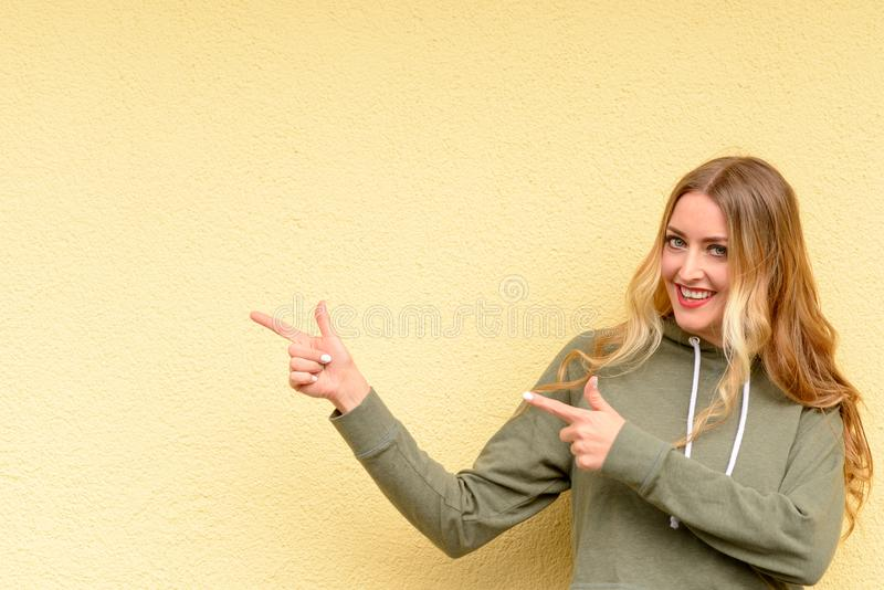 Motivated pretty blond woman pointing to the side royalty free stock photos