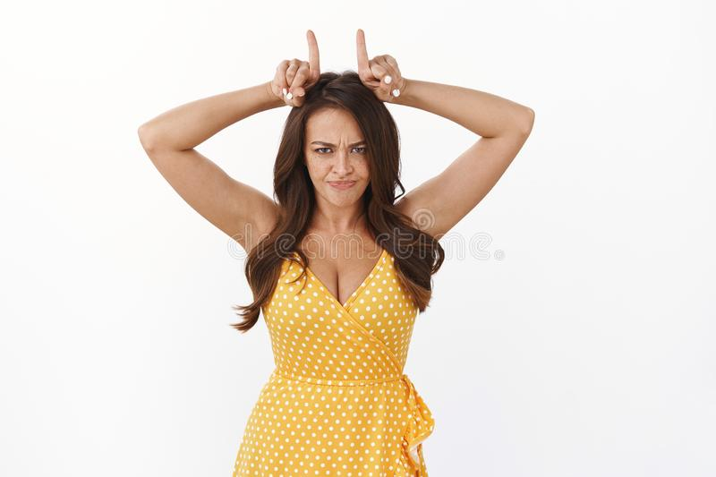 Motivated and stubborn young woman gonna pave her own way to success. Serious-looking ambitious daredevil girl in yellow. Dress, grimacing make angry face and stock photography
