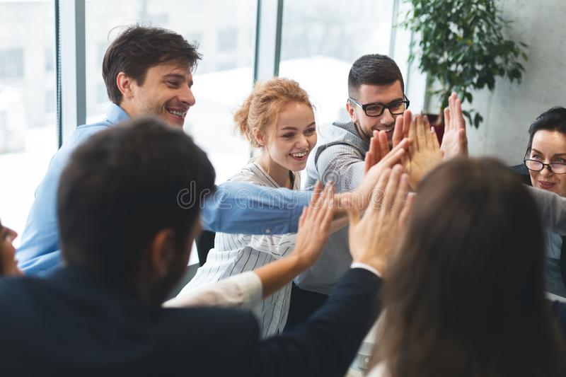 Motivated successful business team giving high five stock images
