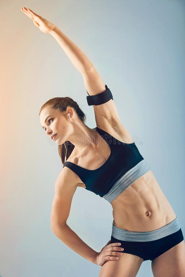 Motivated young sporty woman side bending while warming up royalty free stock images