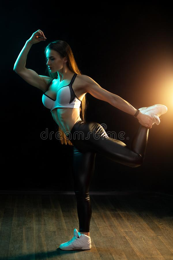 Motivated young woman fitness model posing in neon lights silhouette in the studio. Motivated young woman fitness model posing in neon lights silhouette in the royalty free stock images