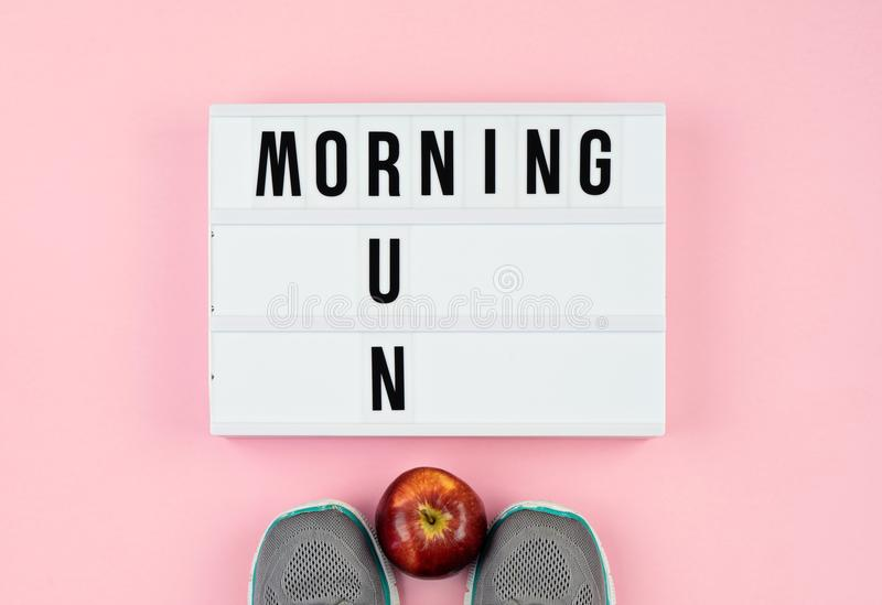 Motivation quotes on light box, apple and sport shoes on the pink royalty free stock photo