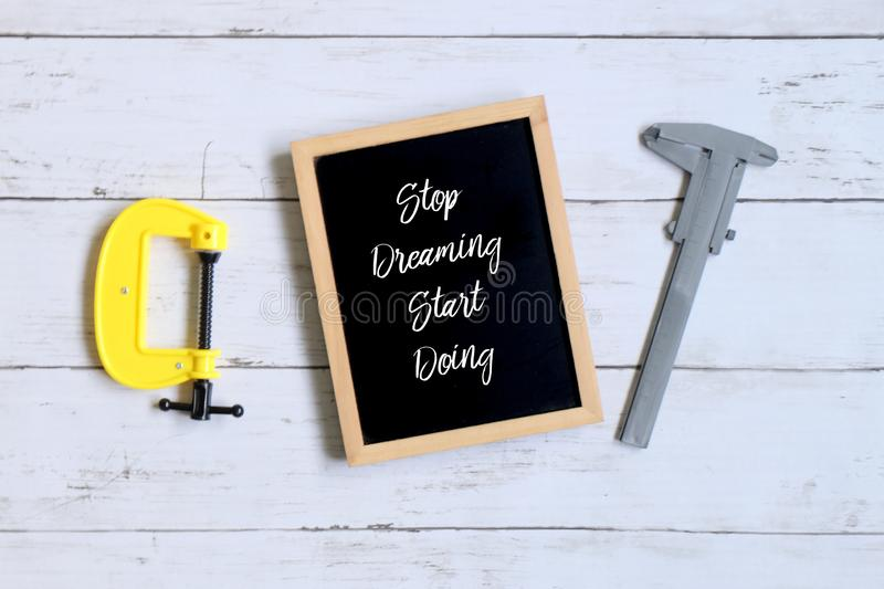 Motivation quotes Stop Dreaming Start Doing on a blackboard. Business and finance concept. royalty free stock photography