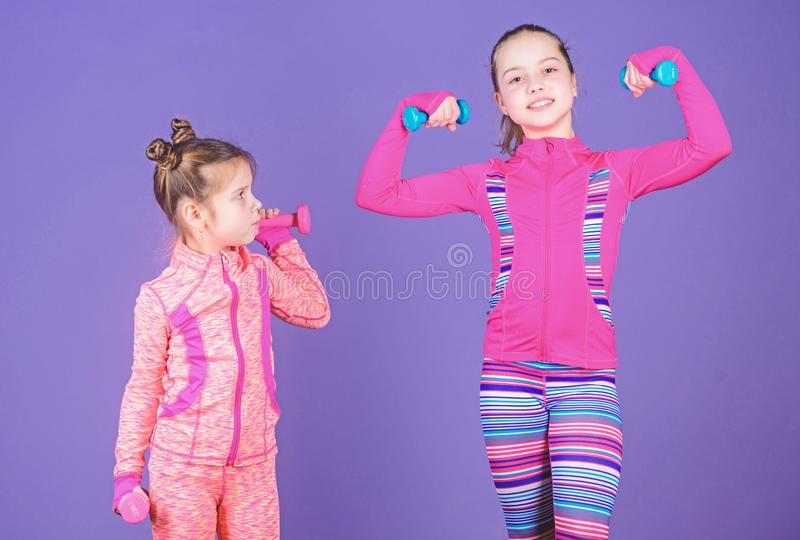 Motivation and sport example concept. Toddler repeat exercise after sister. Sport exercises for kids. Healthy upbringing. Sporty babies. Following her sister royalty free stock photo
