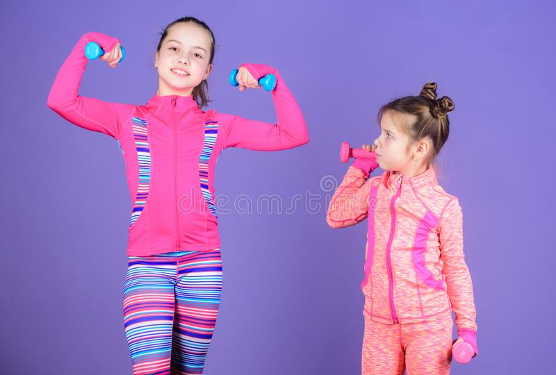 Motivation and sport example concept. Toddler repeat exercise after sister. Sport exercises for kids. Healthy upbringing. Sporty babies. Following her sister stock photos