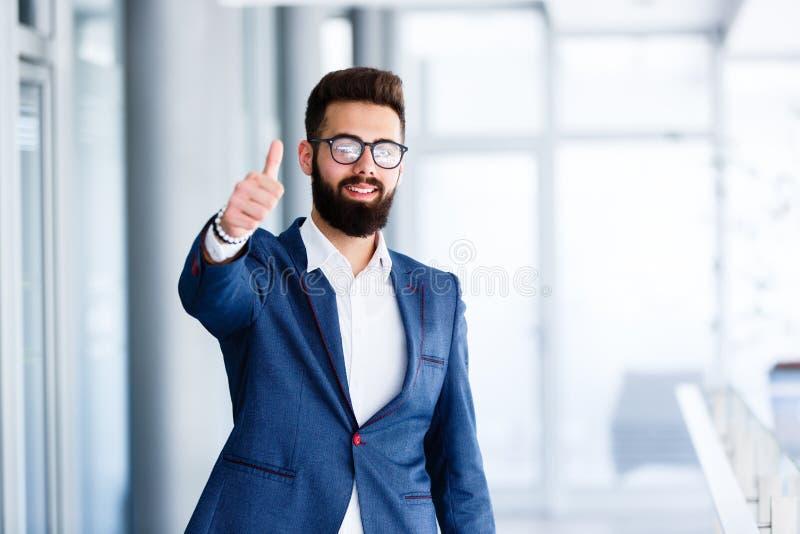 Motivational gest av den unga stiliga affärsmannen arkivbild